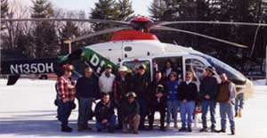 group of people in front of a helicopter