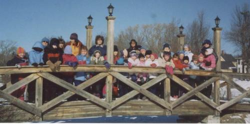 group of kids and adults on a snowy bridge